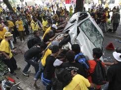 Protesters overturn a police car during Saturday's rally in Kuala Lumpur, Malaysia, to demand electoral reforms.