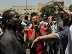 Egyptian protesters chant anti-ruling military council slogans by a an army security barrier in Cairo on Sunday.