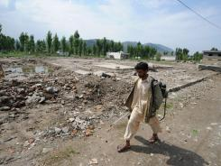 A Pakistani farmer carrying a pesticide spray kit walks past the site of the demolished compound of slain al-Qaeda leader Osama bin Laden in northern Abbottabad on Wednesday.