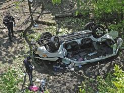 Police investigate the destroyed van that plunged over the Bronx River Parkway in New York on Sunday.