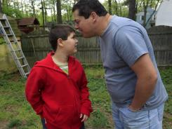 Stuart Chaifetz kisses his son, Akian Chaifetz, 10, as they play in the backyard of their home Wednesday in Cherry Hill, N.J.