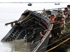 Rescuers pull out the wreckage of a ferry Tuesday that capsized in the Brahmaputra River in India.