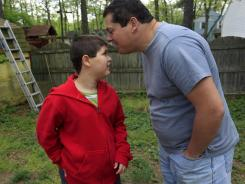 Stuart Chaifetz kisses his son Akian Chaifetz, 10, on the head as they play in the backyard of their home.