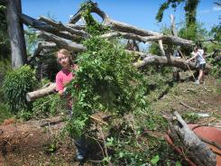 University of Alabama freshman Megan White from New Boston, N.H., helps remove debris from a residence in Tuscaloosa, Ala., on Tuesday. The tornado cleanup efforts are still underway one year later.