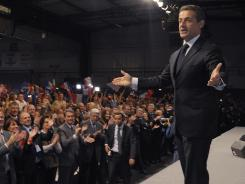 The audience applauds as President Nicolas Sarkozy arrives for his campaign meeting on Sunday in Toulouse.