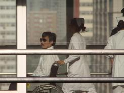 Chinese activist Chen Guangcheng is pushed in a wheelchair Wednesday at a Beijing hospital.