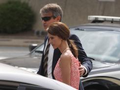 Cheri Young, right, is escorted out of the federal courthouse in Greensboro, N.C., on Monday.