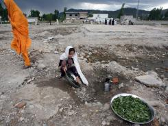 A Pakistani girl washes vegetables at the site of the demolished compound of slain al-Qaeda leader Osama bin Laden in Abbottabad on Tuesday.