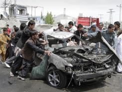 Afghans push a damaged car away from the scene of a militant attack Wednesday in Kabul.