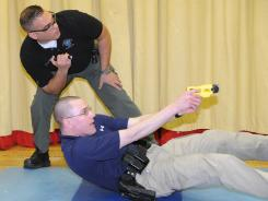 Charles M. Balon, a Taser International Training Academy master instructor, supervises Dan Lewis of Plains Township, Pa., during a February drill for officers that taught them how to instruct their colleagues.