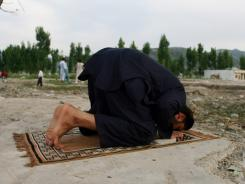 A Pakistani man prays near the site of the demolished compound of slain Al-Qaeda leader Osama bin Laden in Abbottabad, on May 2, 2012, on the anniversary of the death of Osama bin Laden.