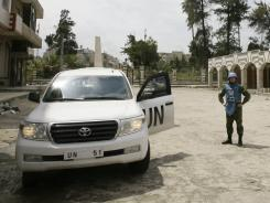 U.N. monitors inspect the restive Khalidiyah district in the central Syrian city of Homs on Thursday.
