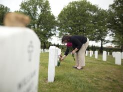 Ami Neiberger-Miller places flowers at the grave site of Marine Cpl. Sean Osterman at Arlington National Cemetery.