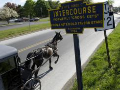 An amish buggy travels by a sign for Intercourse, Pa.