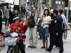 Chinese residents flash victory signs Friday as a police officer asks them to move from outside the hospital where activist lawyer Chen Guangcheng was admitted.