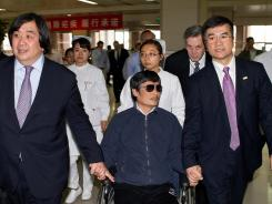 In this handout photograph provided by the U.S. Embassy press office, Chen Guangcheng holds hands Wednesday with U.S. Ambassador to China Gary Locke, right, in Beijing.