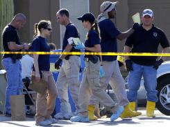Investigators walk inside the police tape Thursday where police say a white supremecist shot four people and himself.