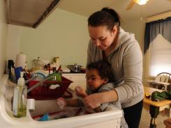 Kathleen Marshall helps two-year-old Kevin wash his hands at their home on Hedley Street in Philadelphia. USA TODAY tested soil in the family's yard and found elevated levels of lead. Kevin's blood-lead level was 7.5 in August 2011, which can cause a decreased IQ and delayed puberty, according to the CDC.