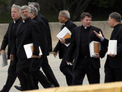 Catholic clergy members depart from Cardinal O'Hara High School on Wednesday in Springfield, Pa. Hundreds of Roman Catholic priests were called to a sudden meeting with Archbishop Charles Chaput as 23 priests suspended over sex-abuse allegations were investigated.