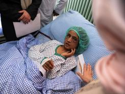 Afghan child bride Sahar Gul, 15, looks at Afghanistan's Minister of Women's Affairs, Husn Banu Ghazanfar, at a hospital in Kabul on December 31, 2011.