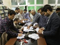 Electoral workers count ballots in a polling station in Tehran, Iran, on Friday.
