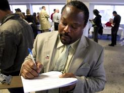 "Teacher Michael Newman fills out union forms to fight a recent ""reduction in force"" letter at a United Teachers Los Angeles meeting in L.A. on April 16."