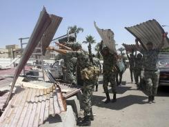 Egyptian Army soldiers clear away scrap metal used by protesters during clashes outside the Ministry of Defense in Cairo.