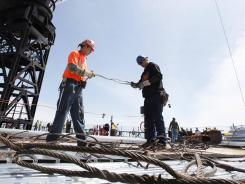 Iron workers Steven Cross, left, and Adam Cross prepare steel cables to lift iron beams on the 100th story of One World Trade Center on Monday in New York City.