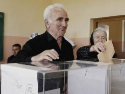 A man casts his ballot at a polling station during the Serb elections in Gracanica, Kosovo.