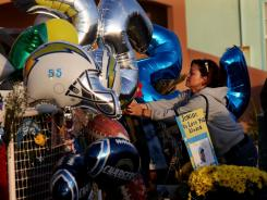 Memorial: Fans pay respect outside Junior Seau's home on Thursday in Oceanside, Calif.
