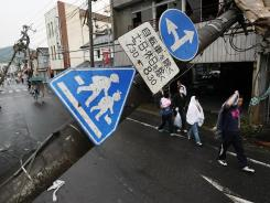 People walk past a collapsed electric pole after a tornado swept through a residential area of Tsukuba, near Tokyo, on Sunday.