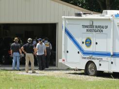 Tennessee Bureau of Investigation agents inspect the home and garage of a woman and her three young daughters who authorities say were abducted near Whiteville, Tenn., on Sunday.