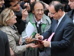 France's new president-elect, Francois Hollande, signs an autograph as he leaves his campaign headquarters Monday.