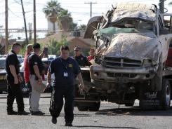 Investigators look at a vehicle that crashed and rolled after a pursuit by Border Patrol agents May 2 in Casa Grande, Ariz.