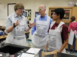 Eighth-graders Kyle Knudsen, left, and Camilo Romero, right, explain their science lab work to Florida Gov. Rick Scott at Carwise Middle School in Palm Harbor, Fla., in April. Science test scores for eighth-graders rose slightly from 2009 to 2011.