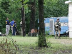 The FBI searches the area around Adam Mayes' home on Monday, after two bodies were discovered in his yard in Union County, Miss.