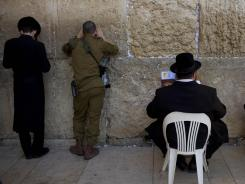 Israeli soldiers and ultra-Orthodox Jewish men pray at the Western Wall in Jerusalem. A practice that has allowed ultra-Orthodox men to avoid military service looms as a test for Prime Minister Benjamin Netanyahu.