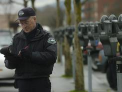Bellingham police parking enforcement officer Brad Crosier writes a ticket on Railroad Street in Bellingham, Wash.