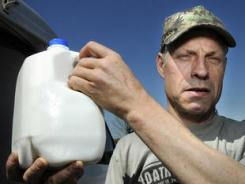 Alvin Schlangen holds a gallon of milk from his delivery truck.