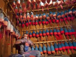 Lobsterman Kendall Delano sands last year's paint off lobster buoys he's painting in his workshop in Friendship, Maine, May 10.