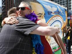 Eric Bennett, left, and Trenton Garris hug as they gather to show support for President Obama during his visit to the Paramount Theater in Seattle on Thursday, one day after announcing his support for same-sex marriage.