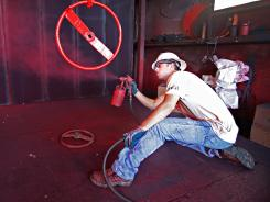 Christopher Dungan paints a valve wheel May 2 at SWECO Wellhead. Dungan, a Purple Heart recipient, says it is hard to find a good job as a veteran.