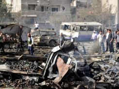 Security forces inspect the site of twin blasts in Damascus on May 10.