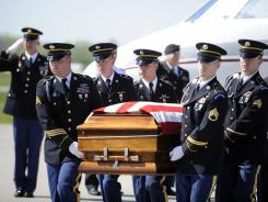 The body of U.S. Army nurse Capt. Bruce Kevin Clark, who died in Afghanistan, carried across the tarmac Saturday at Rochester International Airport.