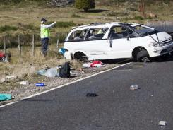 Policemen examine the scene of a minivan crash near Turangi, New Zealand, on Saturday.