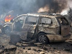 A handout picture released by the Syrian Arab News Agency (SANA) shows burning vehicles at the site of twin blasts in Damascus on Thursday.