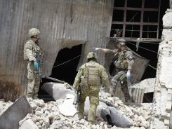 Soldiers part of the NATO forces investigate the scene at a militant attack in Kabul, Afghanistan.