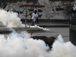 Demonstrators run in front of a wall painted with anti-government graffiti during clashes with riot police firing tear gas Saturday in Bilad al-Qadeem, Bahrain.