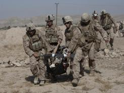 Marines carry a severely wounded Marine, who was hit by an improvised explosive device, to a medevac helicopter.