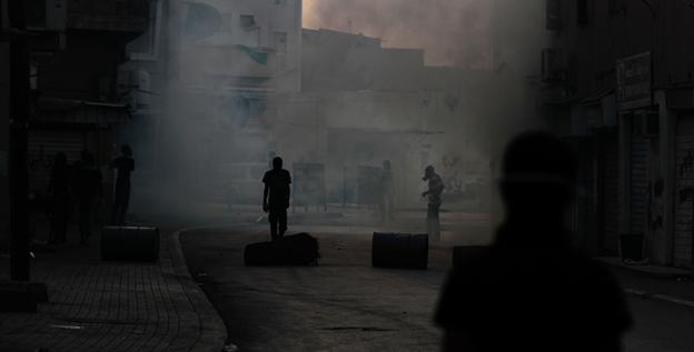 Tear gas fired by riot police during clashes with anti-government demonstrators fills the streets Saturday in Bilad al-Qadeem, Bahrain.